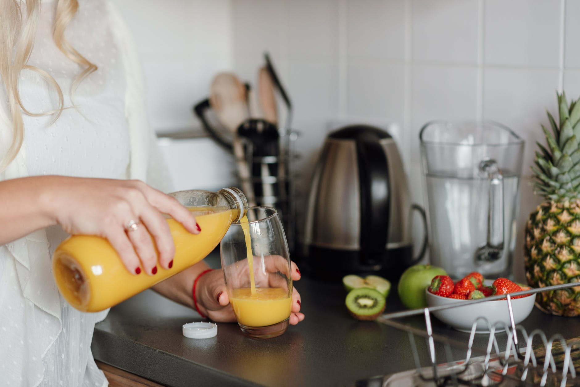 crop woman poring juice standing near table with fruits